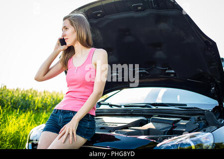Pretty, young woman by the roadside after her car has broken down - Stock Photo