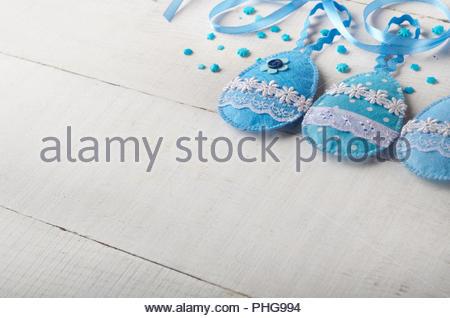 Handmade patchwork blue felt easter eggs on white wooden table - Stock Photo