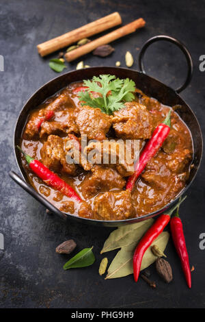 Traditional Indian curry lamb masala as close-up in a Korai - Stock Photo