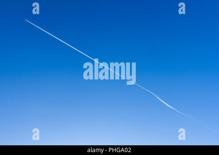 Airplane in the blue sky leaves white stripes behind him - Stock Photo