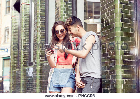 Teenage couple using smart phone together - Stock Photo