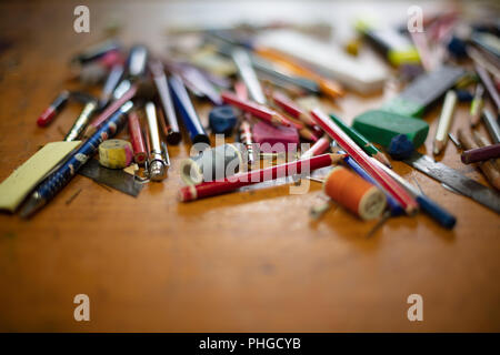 Assorted objects ; colored pencils, pens, crayons, erasers, binder, paper clips, pencil, sharpener, colored pins, and nails, thread rolls, brush, scre - Stock Photo