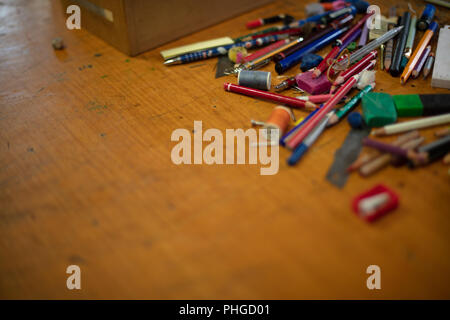 Assorted objects ; colored pencils, pens, crayons, erasers, binder, paper clips, pencil sharpener, colored pins, and nails, thread rolls, brush, screw - Stock Photo