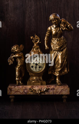 Decorative brass clock with marble pedestal and figurines - Stock Photo