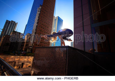 Young woman doing yoga on city rooftop - Stock Photo