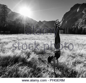 Young woman doing handstand in field by mountains - Stock Photo
