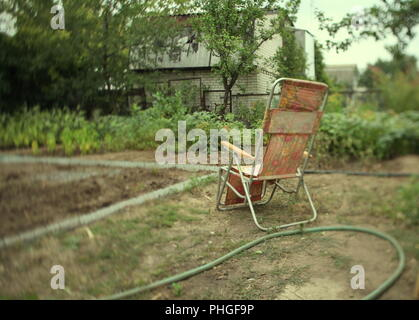 clamshell chair in the garden - Stock Photo