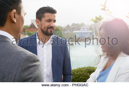 Businesspeople talking during meeting on balcony - Stock Photo
