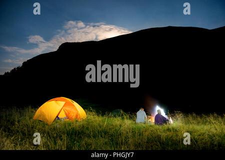 People near illuminated orange tent - Stock Photo