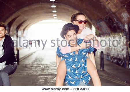 Teenage boy giving girlfriend piggyback ride in tunnel - Stock Photo