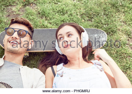 Teenage couple lying on skateboard at park - Stock Photo