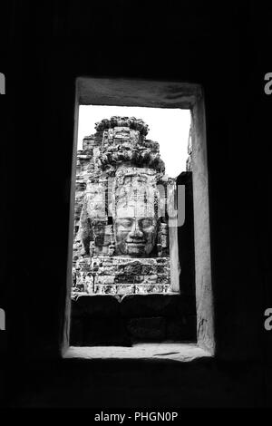 Framed by the stone with buddha face in Angkor Wat in black and white - Stock Photo