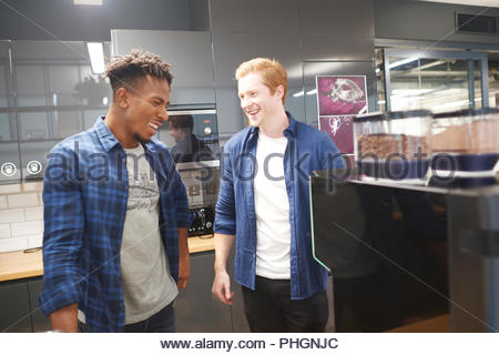 Smiling young businessmen take break in office kitchen - Stock Photo