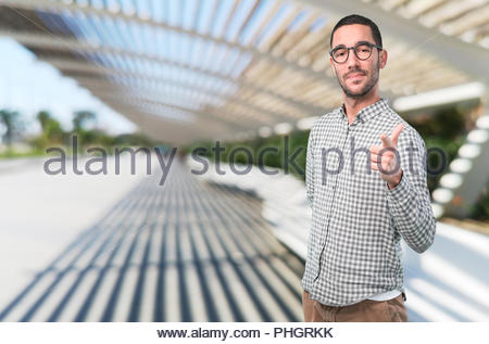 Cool young man pointing with his hand - Stock Photo