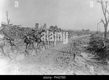 First World War 1914-1918. British soldiers with their bicycles are walking on a muddy road somewhere in France. They are passing demolished buildings and ruins. - Stock Photo
