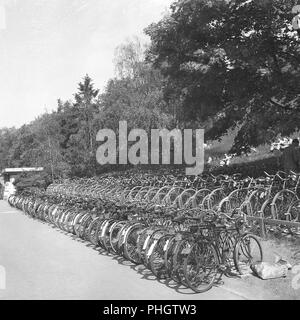 1940s cyclists. Bicycles are parked at a public bath a warm summer day. The bicycles are properly parked in cycle racks. Note the registration signs on the bikes that was a mandatory item at the time.  May 1940.  Photo Kristoffersson 129-11 - Stock Photo