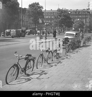 1940s cyclists. Bicycles are parked against the sidewalk in a busy street in Stockholm city. The stand for parking the bicycle without leaning it to something, looks as if it is not yet an item mounted on the bicycles. The bicycles are all leaning agains the kerb of the sidewalk.  May 1940.  Photo Kristoffersson 129-9 - Stock Photo