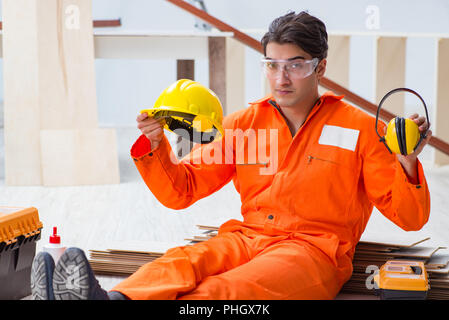 Worker showing the importnace of wearing noise cancelling headph - Stock Photo