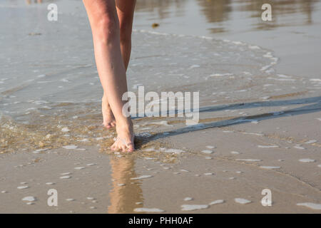 A woman walking along the beach on a Sunny day - Stock Photo