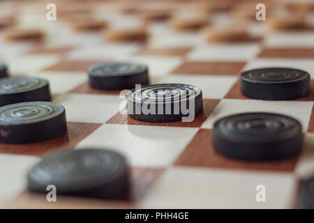 This is a wooden checkers board with black and white pawns game setup ready to play a - Stock Photo