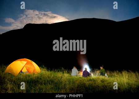 People near illuminated orange tent - Stock Photo