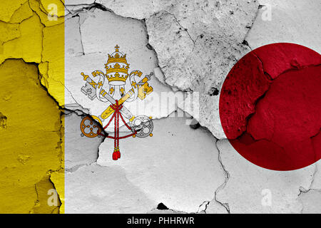 flag of Vatican and Japan painted on cracked wall - Stock Photo