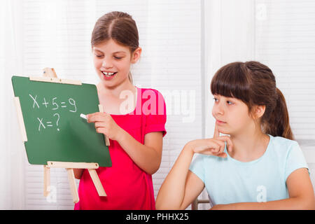 Cute little girls are helping each other with homework. - Stock Photo