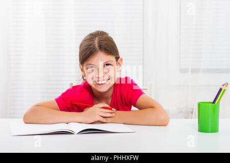 Cute little girl is doing her homework. - Stock Photo
