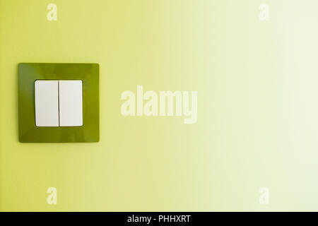 White light switch on a green wall - Stock Photo