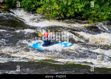 LLANGOLLEN WALES UNITED KINGDOM - AUGUST 27 2018: White water kayaker canoeing through rapids on the River Dee - Stock Photo