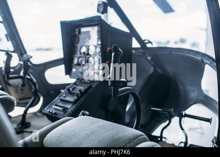 Inside helicopter cabin, control panel, side view from opened door, nobody. Dashboard in cockpit of small copter - Stock Photo