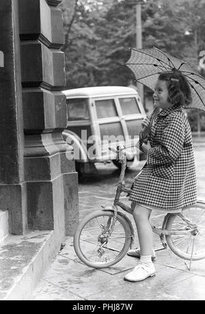 1950s girl on a bicycle. A girl is trying out a new bicycle outside the bicycle shop. She sits happily on the bicycle in the rain under her umbrella.  Sweden 1954.  Photo Kristoffersson 2A-29 - Stock Photo
