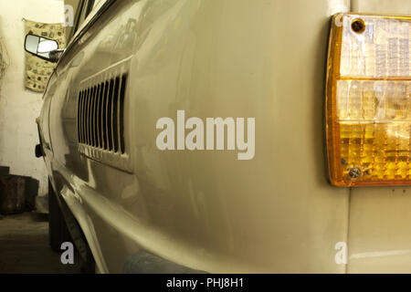 rounded left rear corner of vintage car. left tail light, turn signal and side vent grille - Stock Photo