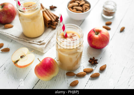 Apple pie protein smoothie drink with almond milk. Homemade apple smoothie with apple pie spices (cinnamon) on white wooden background. - Stock Photo