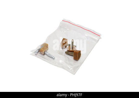 heeltaps in re-sealable plastic bag. isolated; repair kit of brown ribbed plastic parts with metal pin. for shoes on high heel - Stock Photo