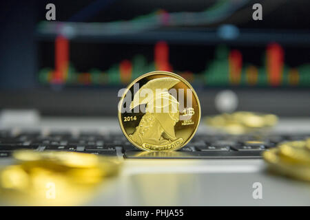 Golden titan bitcoin coin with gold coins lying around on a silver keyboard of laptop and diagram chart graph on a screen as a background. Mining of bitcoins online bussiness. Titans trading - Stock Photo