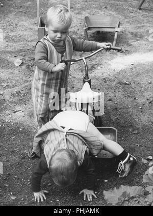 1946s children. Two boys are playing with a tricycle. Sweden 1960s - Stock Photo
