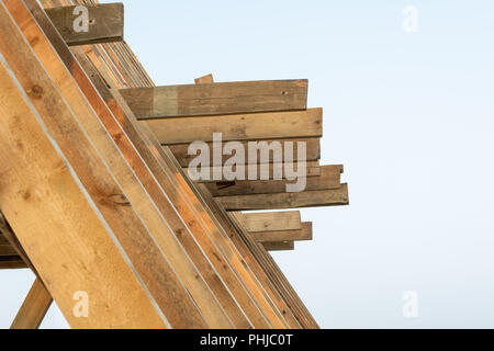 Single Family Home Construction. Building a New Wood Framed House. Wooden rafters against the blue sky at sunset. - Stock Photo