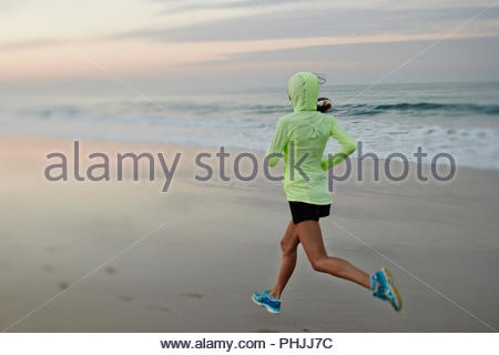 Woman in hoodie jogging on beach - Stock Photo