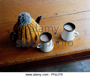 Tea cups and kettle with tea cozy - Stock Photo