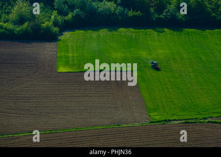 View on hills with cultivated land and woods, a tractor is working on the green field - Stock Photo