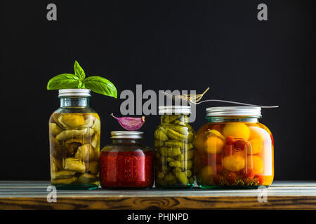 Preserved vegetables on wooden background. Autumn cans for the winter - Stock Photo
