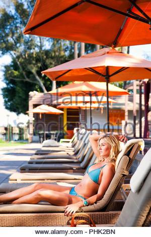 Young woman wearing bikini on lounger - Stock Photo