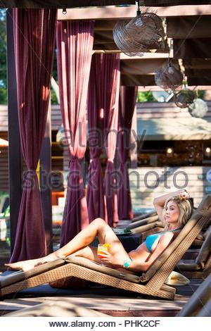 Young woman wearing bikini holding juice on lounger - Stock Photo