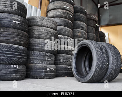 Used car tires stacked in piles at tire fitting service. Wheels for repair shop. Car service concepr - Stock Photo