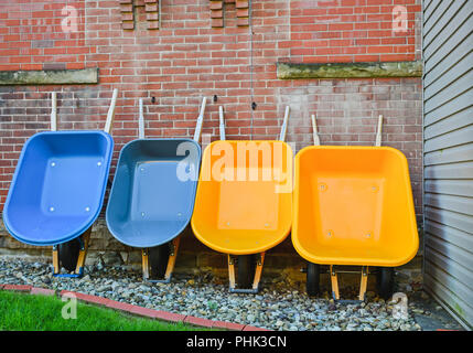 Four wheelbarrows, 2 yellow, 2 blue leaning against a wall - Stock Photo