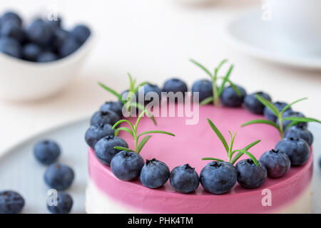 The two-color blueberry mini cheese cake. Round no bake cheesecake, bowl with blueberries, cup of coffee and bowl with sugar. Top of cake decorated by - Stock Photo
