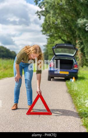 European woman placing hazard warning triangle on road - Stock Photo