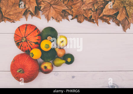 Image of pumpkins,apples and pears on wooden table with autumn leaves.Image is intentionally toned. - Stock Photo