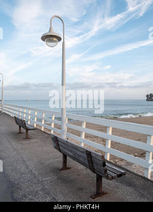 Two Wood Benches On Pier Overlooking the Beach With mostly Sunny Skies - Stock Photo